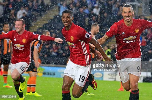 Manchester United's English striker Marcus Rashford celebrates with Manchester United's Swedish striker Zlatan Ibrahimovic and Manchester United's...