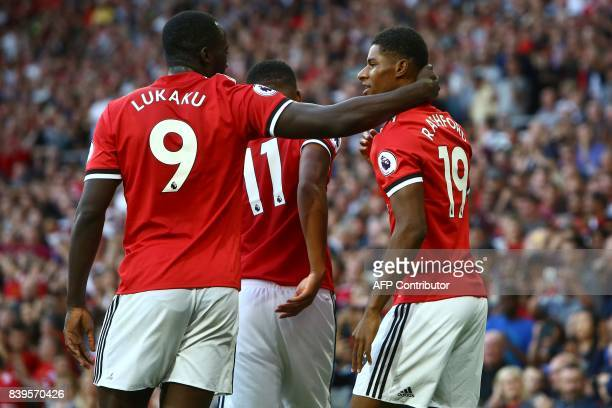 Manchester United's English striker Marcus Rashford celebrates with Manchester United's Belgian striker Romelu Lukaku after scoring the opening goal...