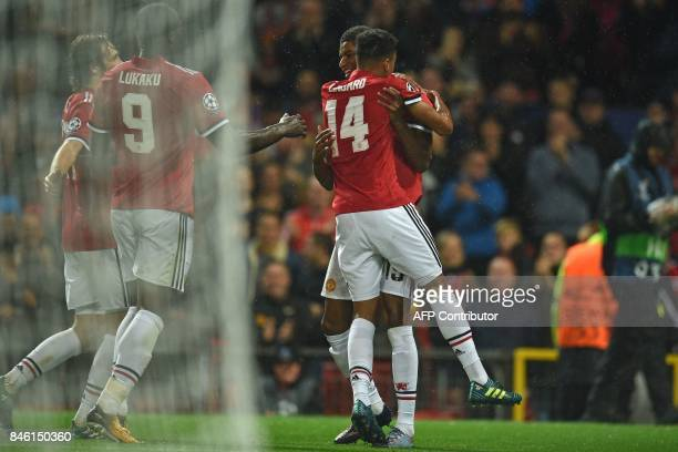 Manchester United's English striker Marcus Rashford celebrates with Manchester United's English midfielder Jesse Lingard and teammates after scoring...