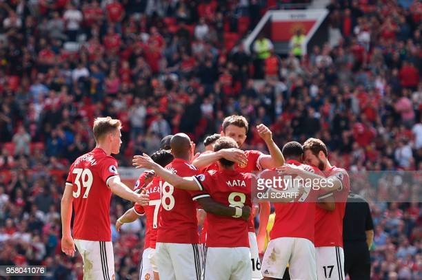 Manchester United's English striker Marcus Rashford celebrates with team mates after scoring the opening goal during the English Premier League...