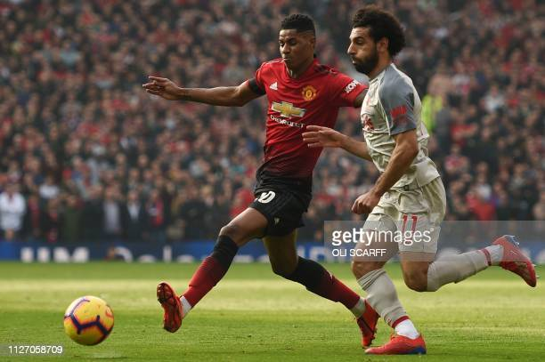 Manchester United's English striker Marcus Rashford challenges Liverpool's Egyptian midfielder Mohamed Salah during the English Premier League...