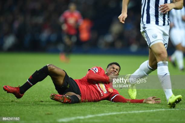 Manchester United's English striker Marcus Rashford falls to the ground after a clash with West Bromwich Albion's Egyptian defender Ahmed Hegazy...