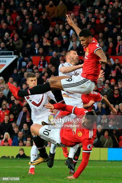 Manchester United's English striker Marcus Rashford gets tangled with Manchester United's Swedish striker Zlatan Ibrahimovic during the English...