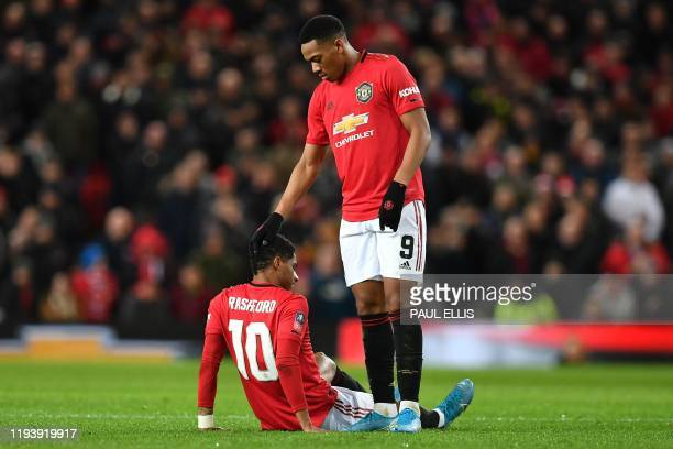 TOPSHOT Manchester United's English striker Marcus Rashford is consoled by Manchester United's French striker Anthony Martial after seeming to pick...