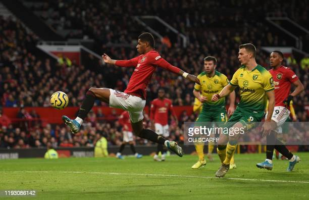 Manchester United's English striker Marcus Rashford leaps to connect with a cross to score the opening goal during the English Premier League...
