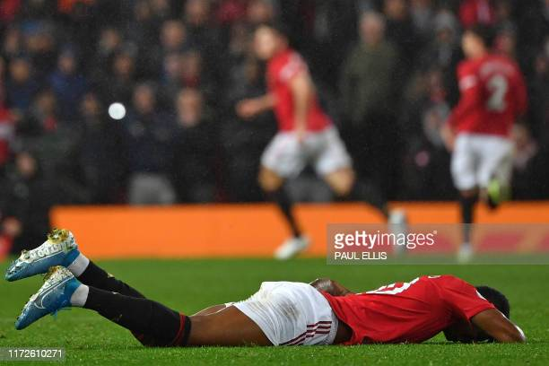 Manchester United's English striker Marcus Rashford lies on the ground injured during the English Premier League football match between Manchester...