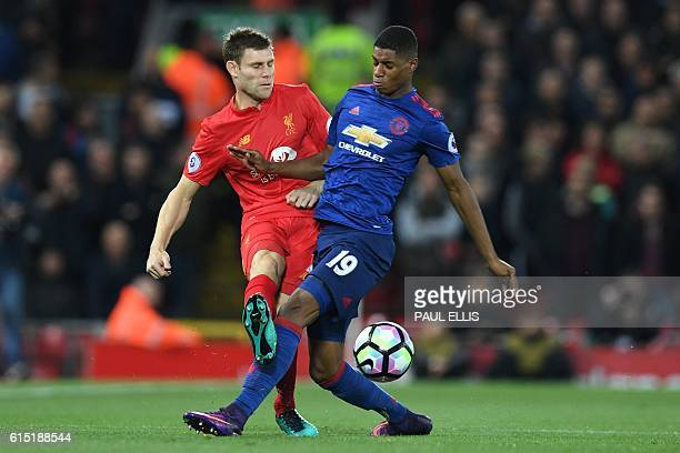 Manchester United's English striker Marcus Rashford makes a rash tackle on Liverpool's English midfielder James Milner early in the English Premier...