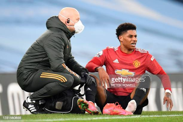 Manchester United's English striker Marcus Rashford reacts after leaving the pitch injured during the English Premier League football match between...