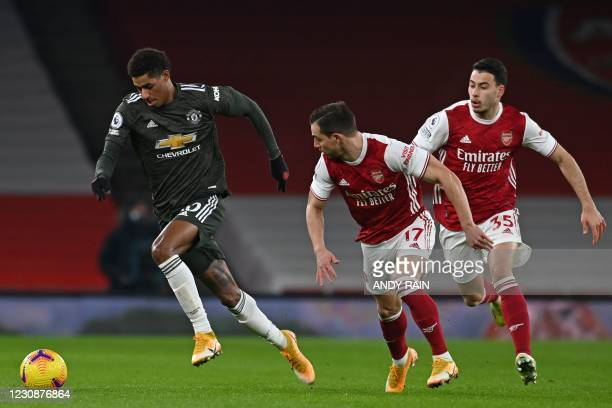 Manchester United's English striker Marcus Rashford runs away from Arsenal's German-born Portuguese defender Cedric Soares and Arsenal's Brazilian...