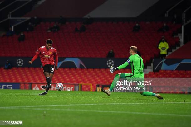Manchester United's English striker Marcus Rashford scores his team's second goal past RB Leipzig's Hungarian goalkeeper Peter Gulacsi during the...