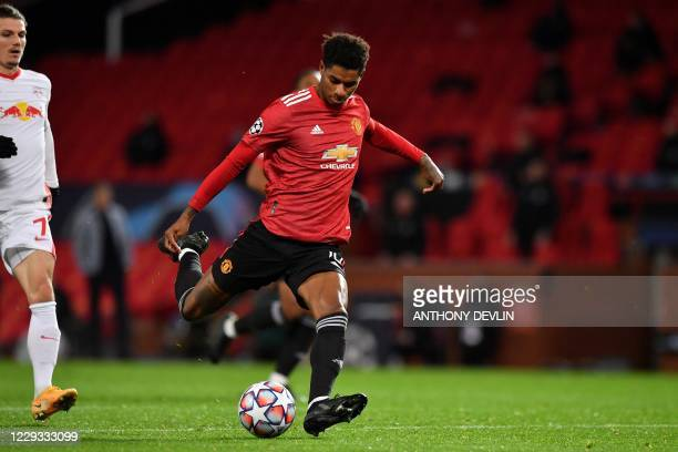 Manchester United's English striker Marcus Rashford scores his team's third goal during the UEFA Champions league group H football match between...