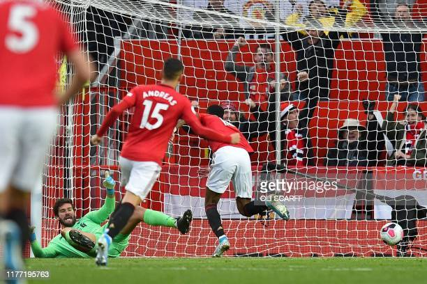 TOPSHOT Manchester United's English striker Marcus Rashford scores the opening goal past Liverpool's Brazilian goalkeeper Alisson Becker during the...