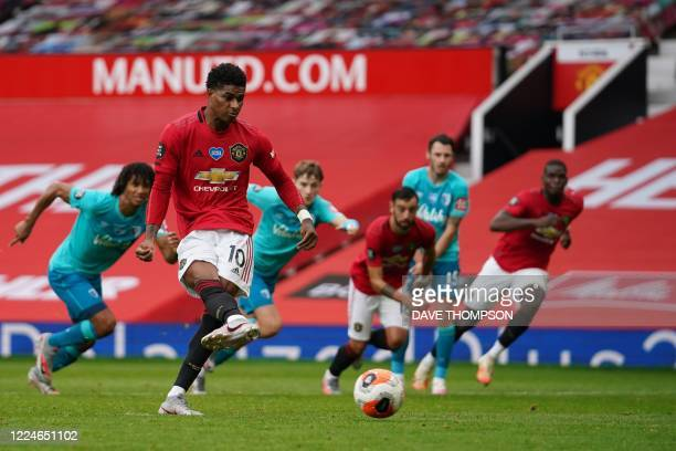 Manchester United's English striker Marcus Rashford shoots a penalty kick and scores during the English Premier League football match between...