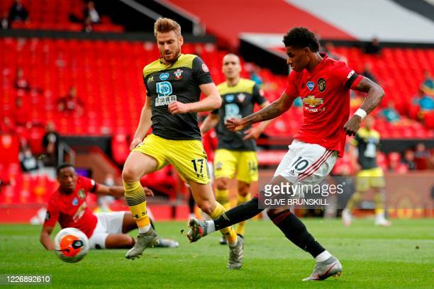 Manchester United's English striker Marcus Rashford shoots to score their first goal during the English Premier League football match between...