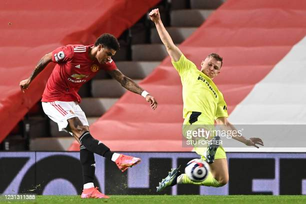 Manchester United's English striker Marcus Rashford shoots to score the opening goal under pressure from Newcastle United's Swedish defender Emil...