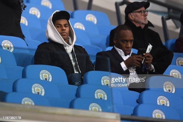 Manchester United's English striker Marcus Rashford sits in Manchester City-branded seats as he watches from the stands during the English League Cup...