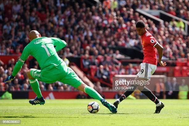 Manchester United's English striker Marcus Rashford slots the ball past Watford's Brazilian goalkeeper Heurelho Gomes to score the opening goal...