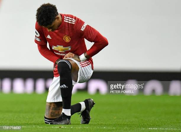 Manchester United's English striker Marcus Rashford takes a knee against racism ahead of the English Premier League football match between Manchester...