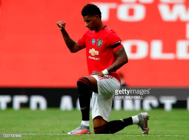 Manchester United's English striker Marcus Rashford takes a knee to protest against racism during the English Premier League football match between...