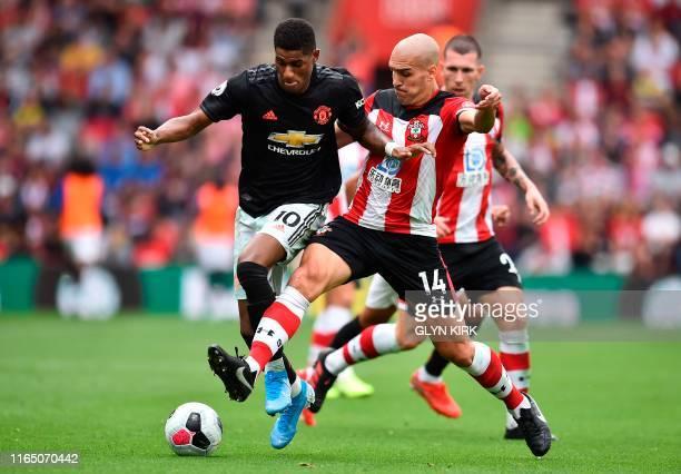 Manchester United's English striker Marcus Rashford takes on Southampton's Spanish midfielder Oriol Romeu during the English Premier League football...