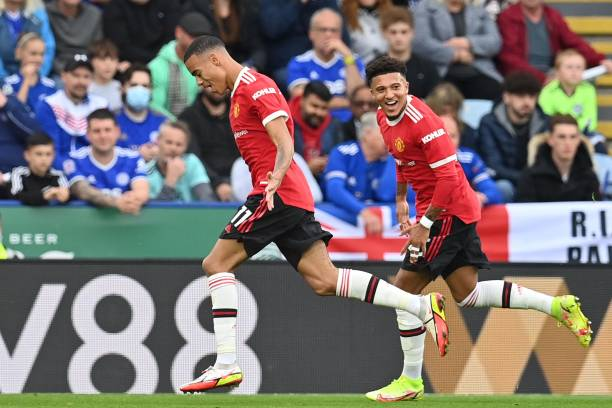 Manchester United's English striker Mason Greenwood celebrates scoring the opening goal with Manchester United's English striker Jadon Sancho during...