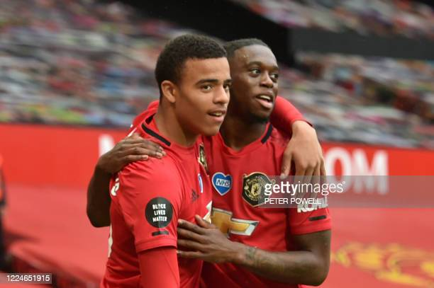 Manchester United's English striker Mason Greenwood celebrates with Manchester United's English defender Aaron Wan-Bissaka after scoring a goal...