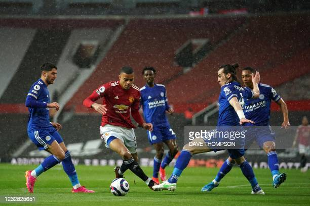 Manchester United's English striker Mason Greenwood manouvres through defenders on his way to scoring his team's opening goal during the English...
