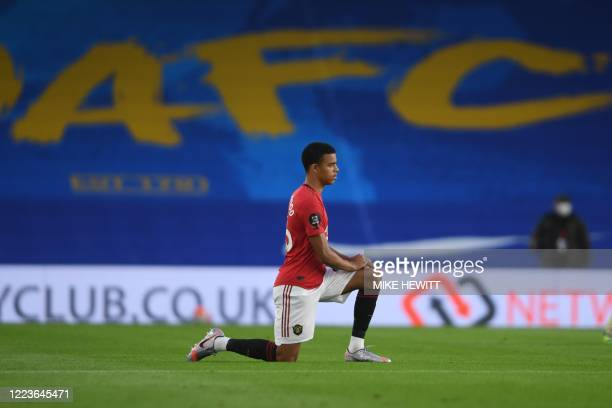 Manchester United's English striker Mason Greenwood takes a knee against racism and to support the Black Lives Matter movement before kick off of the...