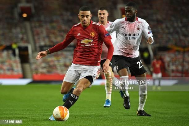 Manchester United's English striker Mason Greenwood takes on AC Milan's Canada-born English defender Fikayo Tomori during the UEFA Europa League...