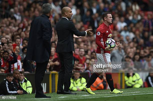 Manchester United's English striker Wayne Rooney and Manchester City's Spanish manager Pep Guardiola clash on the touchline as Rooney retrieves the...