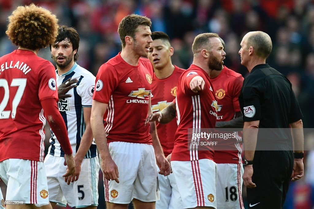 Manchester United's English striker Wayne Rooney (2R) and Manchester United's English midfielder Michael Carrick (3R) talk with referee Mike Dean (R) during the English Premier League football match between Manchester United and West Bromwich Albion at Old Trafford in Manchester, north west England, on April 1, 2017. / AFP PHOTO / Oli SCARFF / RESTRICTED TO EDITORIAL USE. No use with unauthorized audio, video, data, fixture lists, club/league logos or 'live' services. Online in-match use limited to 75 images, no video emulation. No use in betting, games or single club/league/player publications. /