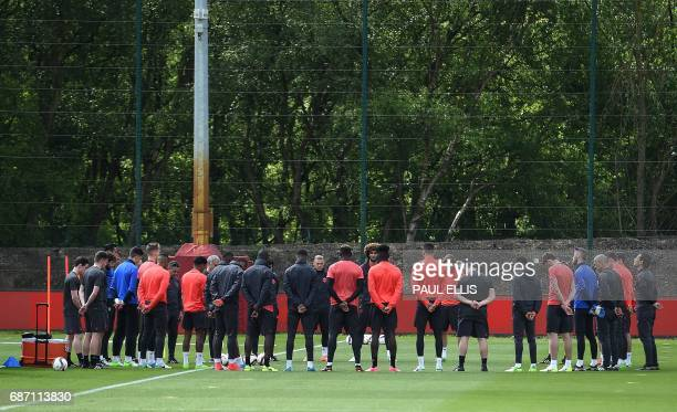 TOPSHOT Manchester United's English striker Wayne Rooney and Manchester United's Belgian midfielder Marouane Fellaini stand with teammates as they...