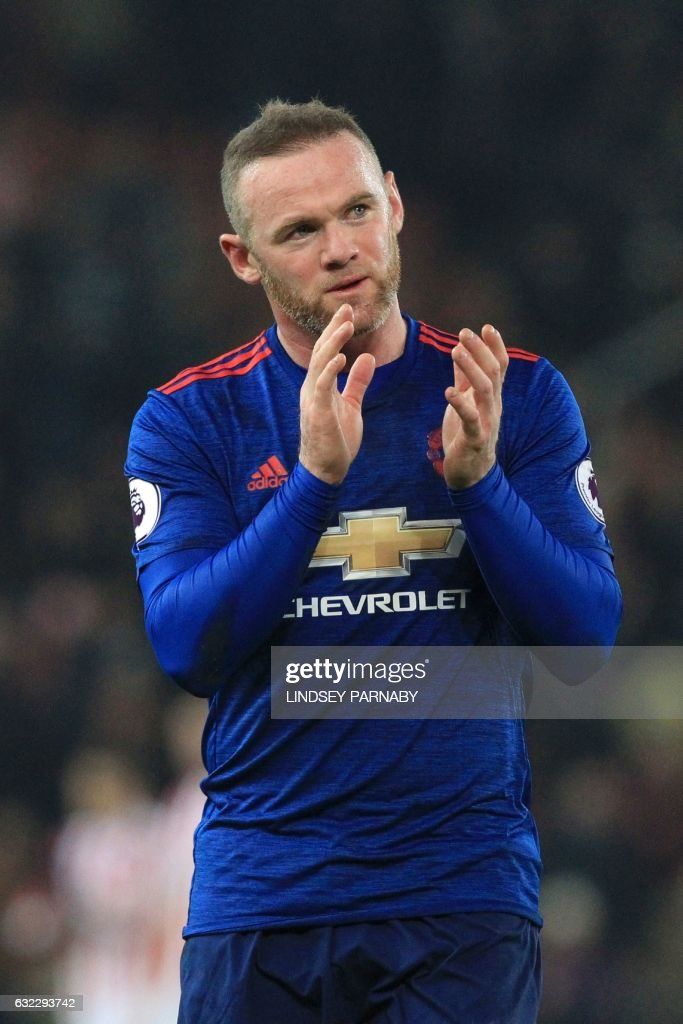 Manchester United's English striker Wayne Rooney applauds at the end of the match after earning United a 1-1 draw by scoring his 250th goal to make him the club's all-time record goal scorerer in the English Premier League football match between Stoke City and Manchester United at the Bet365 Stadium in Stoke-on-Trent, central England on January 21, 2017. / AFP / Lindsey PARNABY / RESTRICTED TO EDITORIAL USE. No use with unauthorized audio, video, data, fixture lists, club/league logos or 'live' services. Online in-match use limited to 75 images, no video emulation. No use in betting, games or single club/league/player publications. /