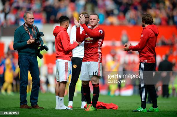 Manchester United's English striker Wayne Rooney applauds the fans at the end of the English Premier League football match between Manchester United...