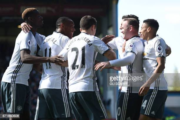 Manchester United's English striker Wayne Rooney celebrates with teammates after scoring during the English Premier League football match between...