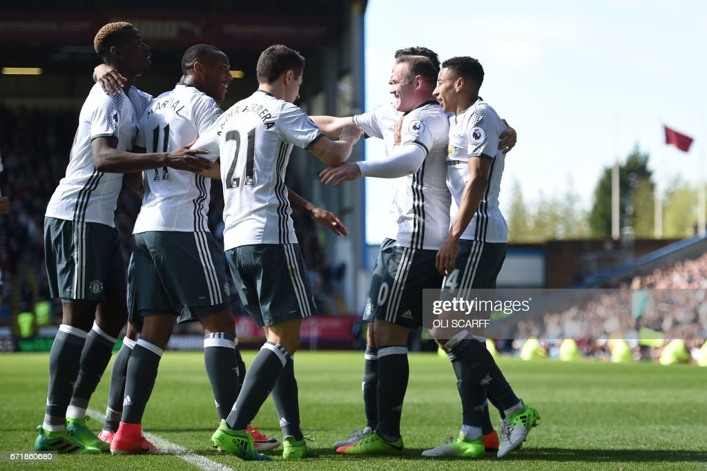 Manchester United's English striker Wayne Rooney (2R) celebrates with teammates after scoring during the English Premier League football match between Burnley and Manchester United at Turf Moor in Burnley, north west England on April 23, 2017. / AFP PHOTO / Oli SCARFF / RESTRICTED TO EDITORIAL USE. No use with unauthorized audio, video, data, fixture lists, club/league logos or 'live' services. Online in-match use limited to 75 images, no video emulation. No use in betting, games or single club/league/player publications. /