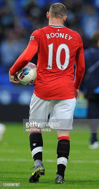 Manchester United's English striker Wayne Rooney claims the match ball having scored a hattrick for the second Premier League game in succession...