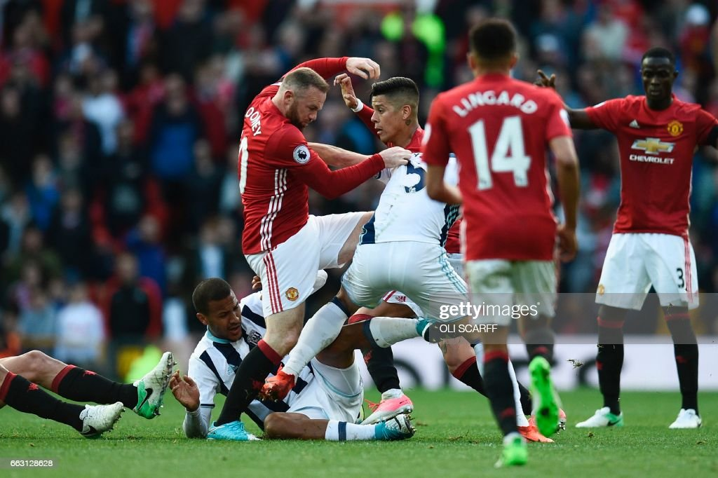 Manchester United's English striker Wayne Rooney (CL) clashes with West Bromwich Albion's Argentinian midfielder Claudio Yacob (CR) and West Bromwich Albion's Venezuelan striker Salomon Rondon (floor) during the English Premier League football match between Manchester United and West Bromwich Albion at Old Trafford in Manchester, north west England, on April 1, 2017. / AFP PHOTO / Oli SCARFF / RESTRICTED TO EDITORIAL USE. No use with unauthorized audio, video, data, fixture lists, club/league logos or 'live' services. Online in-match use limited to 75 images, no video emulation. No use in betting, games or single club/league/player publications. /