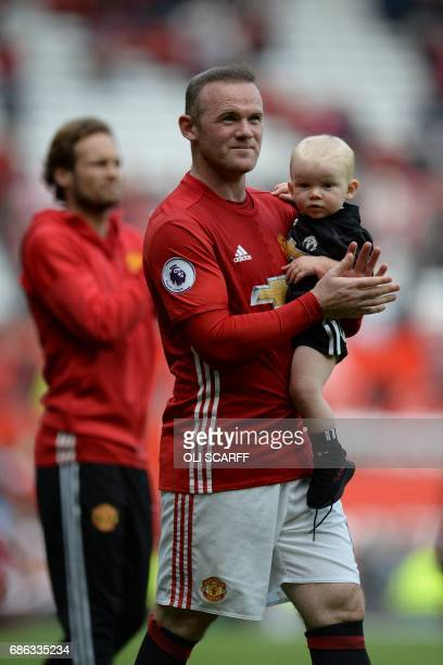 Manchester United's English striker Wayne Rooney comes on the pitch carrying his son Kit on the pitch to applaud the fans at the end of the English...