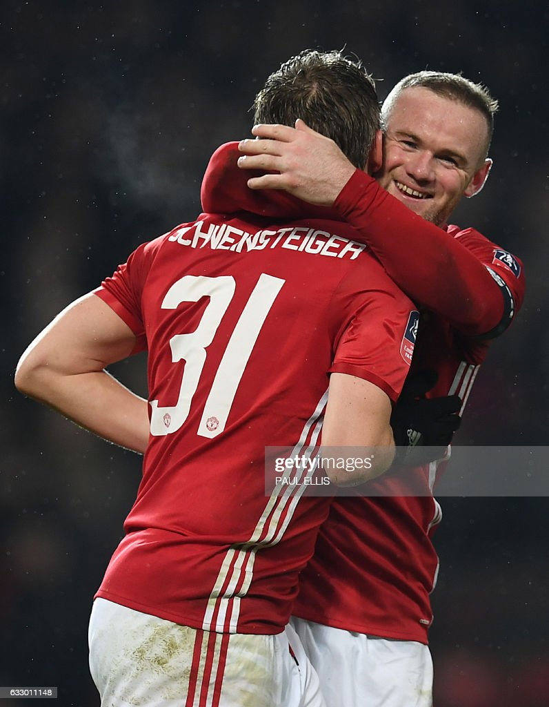 Manchester United's English striker Wayne Rooney (R) embraces Manchester United's German midfielder Bastian Schweinsteiger (L) as they celebrate after Schweinsteiger scored their fourth goal during the English FA Cup fourth round football match between Manchester United and Wigan Athletic at Old Trafford in Manchester, north west England, on January 29, 2017. / AFP / Paul ELLIS / RESTRICTED TO EDITORIAL USE. No use with unauthorized audio, video, data, fixture lists, club/league logos or 'live' services. Online in-match use limited to 75 images, no video emulation. No use in betting, games or single club/league/player publications. /