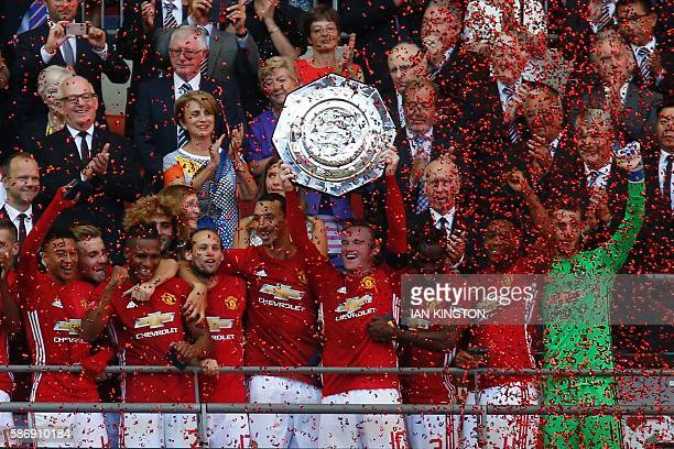 Manchester United's English striker Wayne Rooney holds up the Community Shield during the trophy presentation after Manchester United beat Leicester...