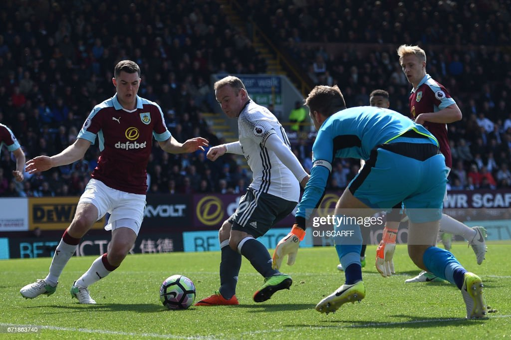 Manchester United's English striker Wayne Rooney (C) scores during the English Premier League football match between Burnley and Manchester United at Turf Moor in Burnley, north west England on April 23, 2017. / AFP PHOTO / Oli SCARFF / RESTRICTED TO EDITORIAL USE. No use with unauthorized audio, video, data, fixture lists, club/league logos or 'live' services. Online in-match use limited to 75 images, no video emulation. No use in betting, games or single club/league/player publications. /