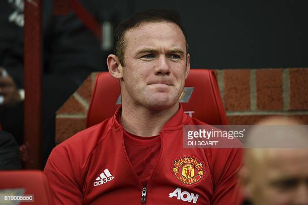 Manchester United's English striker Wayne Rooney sits on the substitutes bench before the start of the English Premier League football match between...