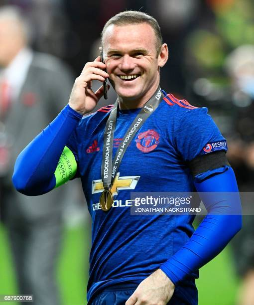 Manchester United's English striker Wayne Rooney speaks on the phone while celebrating after the UEFA Europa League final football match Ajax...