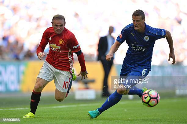 Manchester United's English striker Wayne Rooney takes on Leicester City's German defender Robert Huth during the FA Community Shield football match...