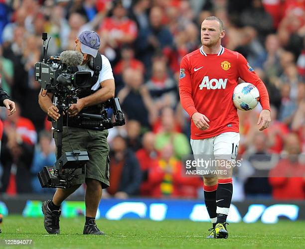 Manchester United's English striker Wayne Rooney walks off with the match ball after scoring a hat trick during the English Premier League football...