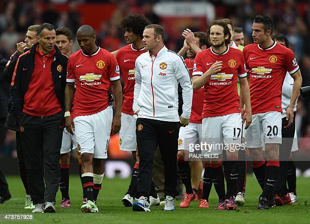 Manchester United's English striker Wayne Rooney walks on the pitch with teammates after the English Premier League football match between Manchester...
