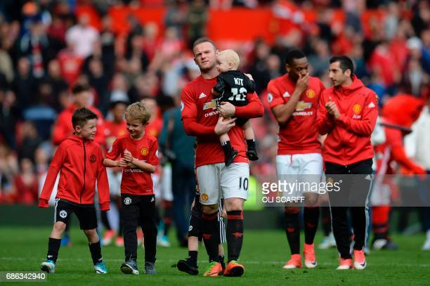 Manchester United's English striker Wayne Rooney walks on the pitch carrying his son Kit to applaud the fans at the end of the English Premier League...