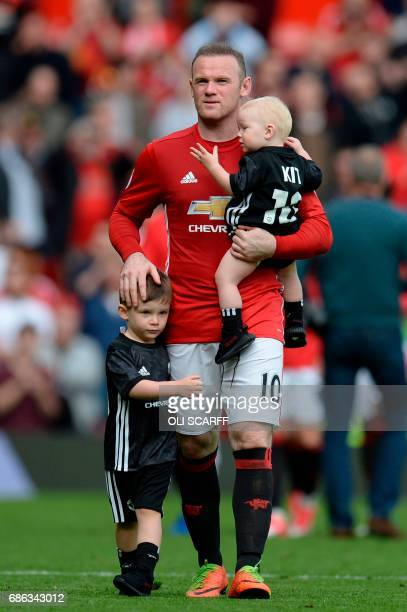 Manchester United's English striker Wayne Rooney walks on the pitch carrying his son Kit and with his son Klay to applaud the fans at the end of the...