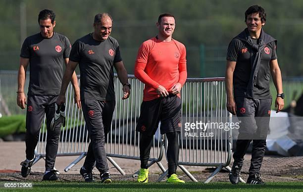 Manchester United's English striker Wayne Rooney walks with new goalkeeping coach Emilio Alvarez Blanco and coaching staff Silvino Louro and Rui...